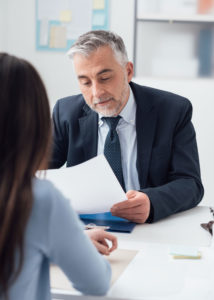 An HR professional sits with a new hire and goes over paperwork